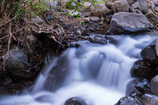 Pure water stream with smooth flow over rocky mountain terrain in the Kakopetria forest in Troodos, Cyprus.
