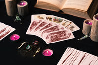 Candles and old tarot cards on black silk vintage look