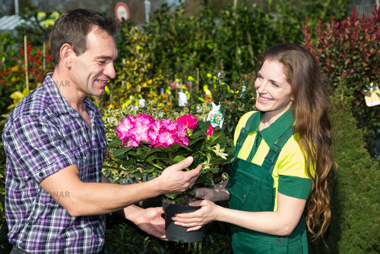 Female florist hands flower to customer in shop