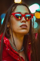 Outdoor fashion portrait of glamour young woman with braided hair wears red down jacket and fashion red sunglasses on neon street lights. Night club fashion