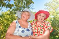 Walk in the garden. Two retired women best friends in hats walk happily in the garden.