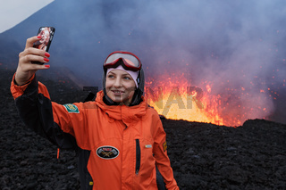 Eruption Tolbachik Volcano on Kamchatka Peninsula, girl photographed selfie on background lava lake in crater volcano