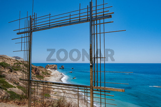 Petra tou Romiou, Aphrodite's birthplace in Paphos, Cyprus behind a framed construction
