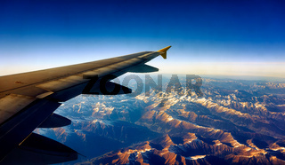View from Airplane Window on a mountain landscape with snow and airplane wing