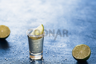 Shot of tequila with salt and lime. Single glass of mexican drink