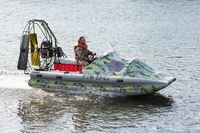 Man in camouflage uniforms and life jacket riding airboat along water surface