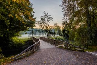 Brücke über den Fluss Ilm für Fußgänger in Weimar im Park an der Ilm am Morgen im Herbst mit Nebel
