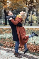 Man lifting a girl hugged laughing in the autumn park with a cute hug. Outdoor shot of a young couple in love having great time having a hug in a autumn park. Close up full length.Tinted image
