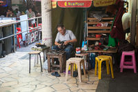 Singapore, A cobbler repairs shoes at his street stall in Chinatown