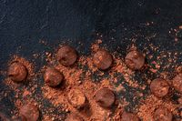 Chocolate truffles, shot from above on a black background