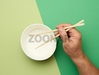 Pair of wooden chopsticks in a male hand and empty paper plate on a green background