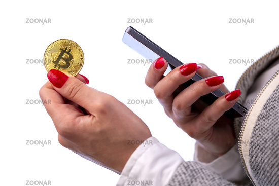Bitcoin coin in woman's hand and smartphone