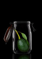 An Avocado with stem and leaf in a glass storage or canning jar isolated on black with reflection, w