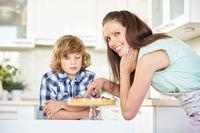 Mutter neben Kind kostet von Kuchen