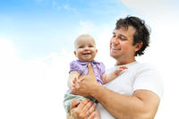 Happy father with baby in rural field