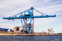 Massive blue crane unload cargo in a seaport in Sweden