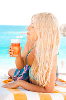 Woman with blond hair enjoying cocktail drink and beach lifestyle in summertime, holiday travel and leisure