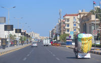 City panorama with street cars about buildings in Hurghada. Modern city with cars on highway.