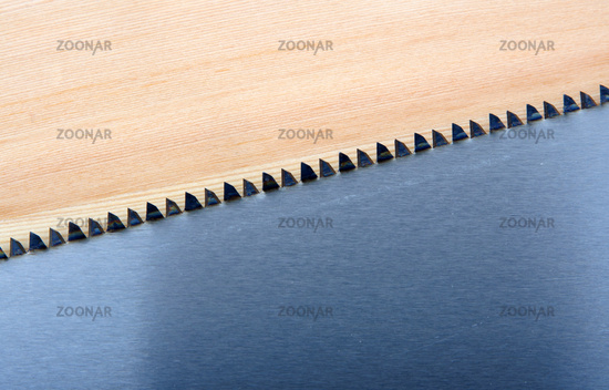An image of hand saw on wooden background
