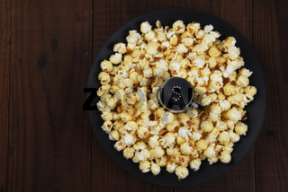 Overhead shot of a salt shaker in a shallow bowl surrounded by fresh made popcorn. Horizontal format on rustic dark table with copy space.