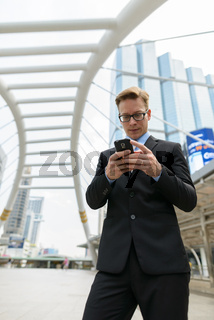 Young handsome blond businessman with eyeglasses using phone in the city outdoors