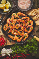 Tasty appetizing roasted shrimps prawns with spices on pan with ingredients on rusty background