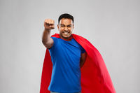 indian man in superhero cape flying over grey