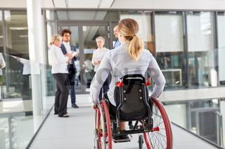 Frau im Rollstuhl im barrierefreien Büro unterwegs