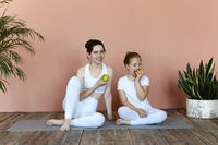 Smiling mother and daughter eating fruits after practicing yoga together