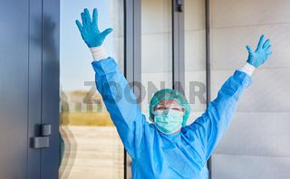Arzt in Schutzkleidung jubelt vor Klinik nach Coronavirus Erfolg