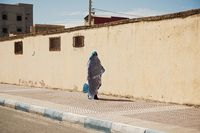 Women walking down the street, wearing beautiful blue and white Arab clothes. Buildings background.