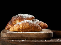 baked crispy croissants sprinkled with powdered sugar lie on a wooden kitchen board