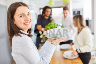 Frau hilft beim Tisch decken mit Geschirr tragen