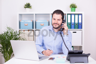 Businessman working indoors at home office. Work, communication and business concept.