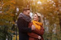 Portrait of a couple in love. Handsome man and a woman hugged from behind smile looking at each other in the autumn park. Outdoor shot of a young couple in love having great time. Autumn toned image