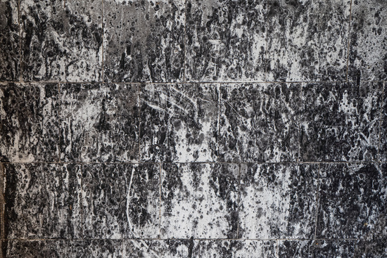Abstract grunge background. White and black spotted tiled wall after fire. High quality photo
