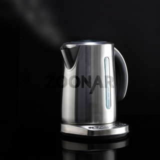 Modern kettle with steam on black reflective surface