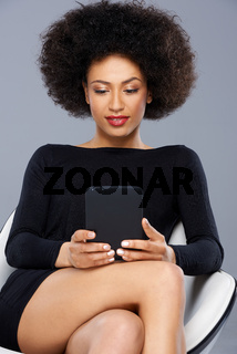 Beautiful African American woman reading a tablet