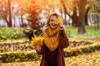 Happy hiding eye woman with a yellowed leaf in yellow knitted beret with autumn leaves in hand and fall yellow garden or park. Beautiful smiling young woman in autumn foliage