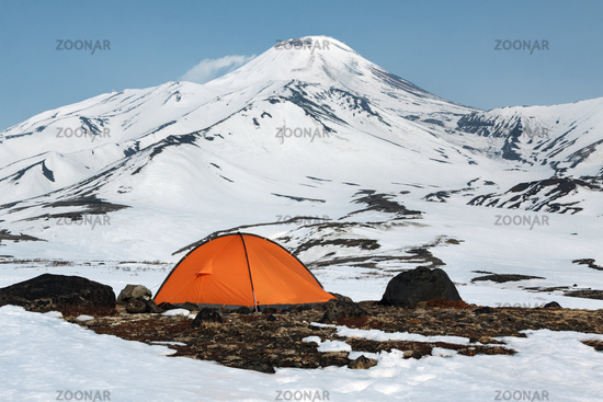 Orange camping tent stands at foot of volcano
