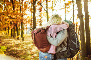 Embrace of couple of travelers, Man and woman with backpacks hugging while standing in the autumn forest. Copy space at left side