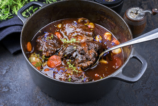 Traditional German braised beef cheeks in brown red wine sauce with carrots and onions offered as closeup in a cast iron Dutch oven on an old rustic board
