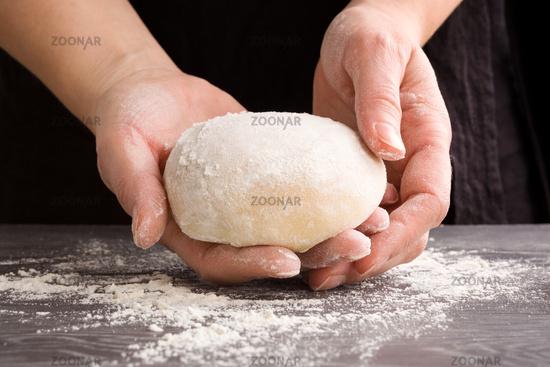Female hands making homemade dough.