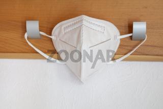 FFP2 Atemschutzmaske hängt an Garderobenhaken