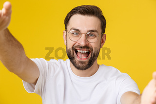 Close up portrait of a cheerful bearded man taking selfie over white background.