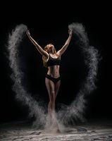 Slim female dancer throwing dust in air