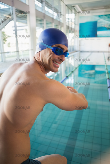 Portrait of shirtless swimmer by pool at leisure center