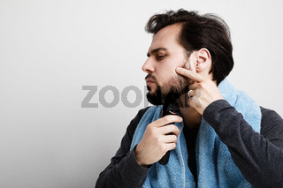 Portrait of handsome young man shaving his beard in bathroom, holding shaver machine. Space for text.