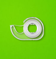 Scotch tape dispenser isolated on green background