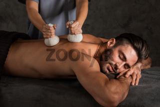 Man getting dry herbs massage